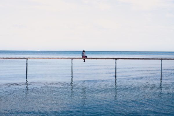 A person sitting in the middle of a long dock