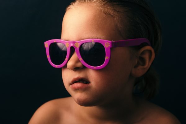 Picture of a child wearing a pink sunglasses