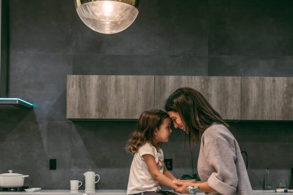 A picture of a mother and child in the kitchen table