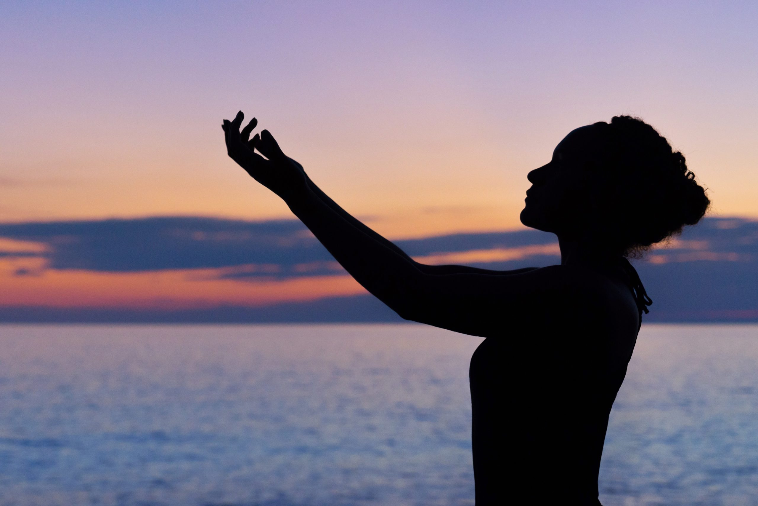 Silhouette of a woman with raised arms