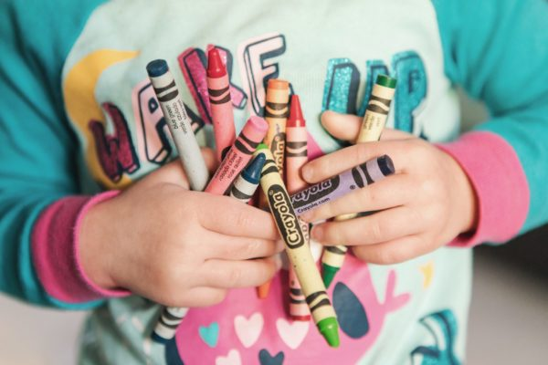 Picture of a child holding several big crayons