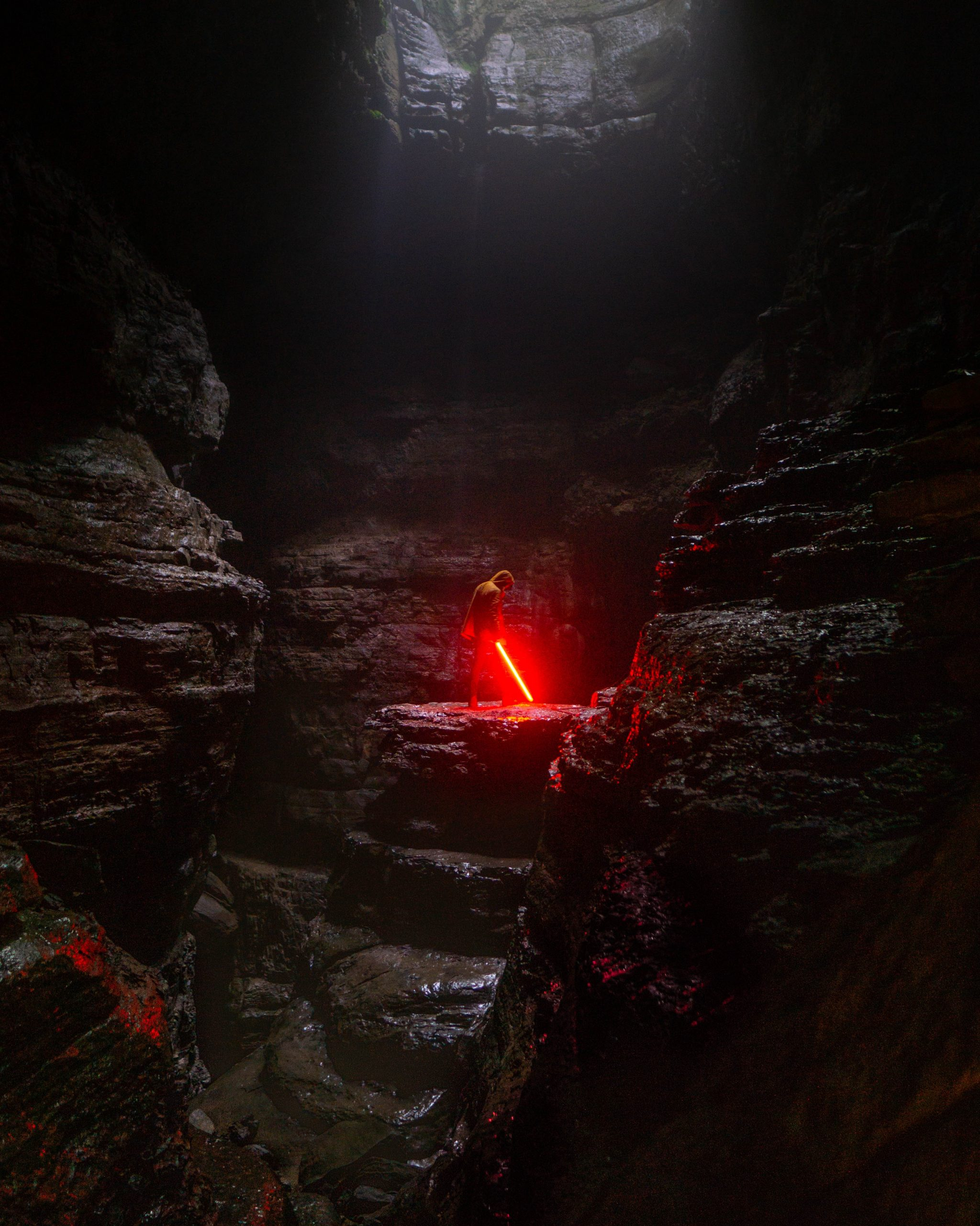 A Jedi holding a red light saber in a cave