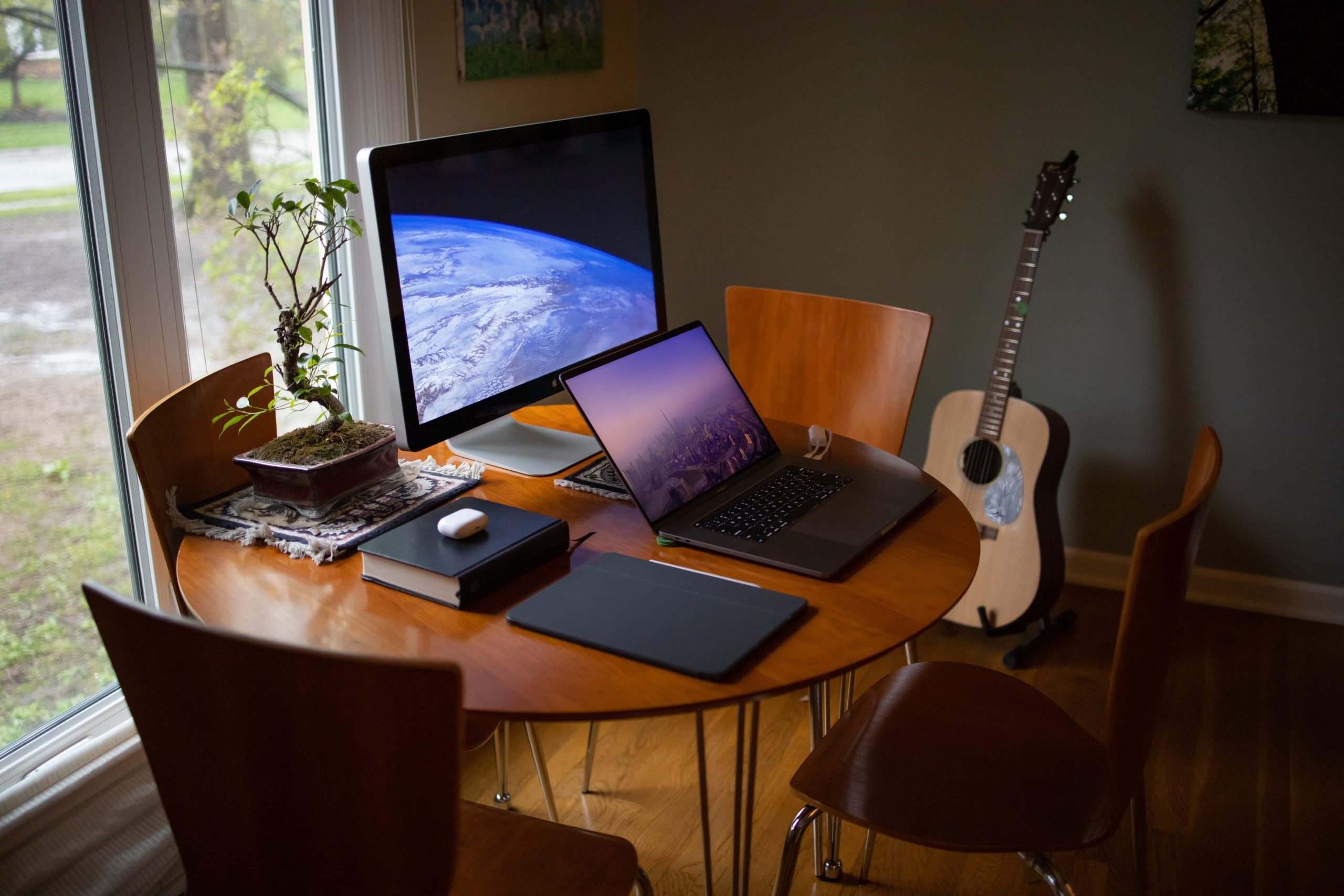 A laptop beside a monitor, book, potted plant and tablet