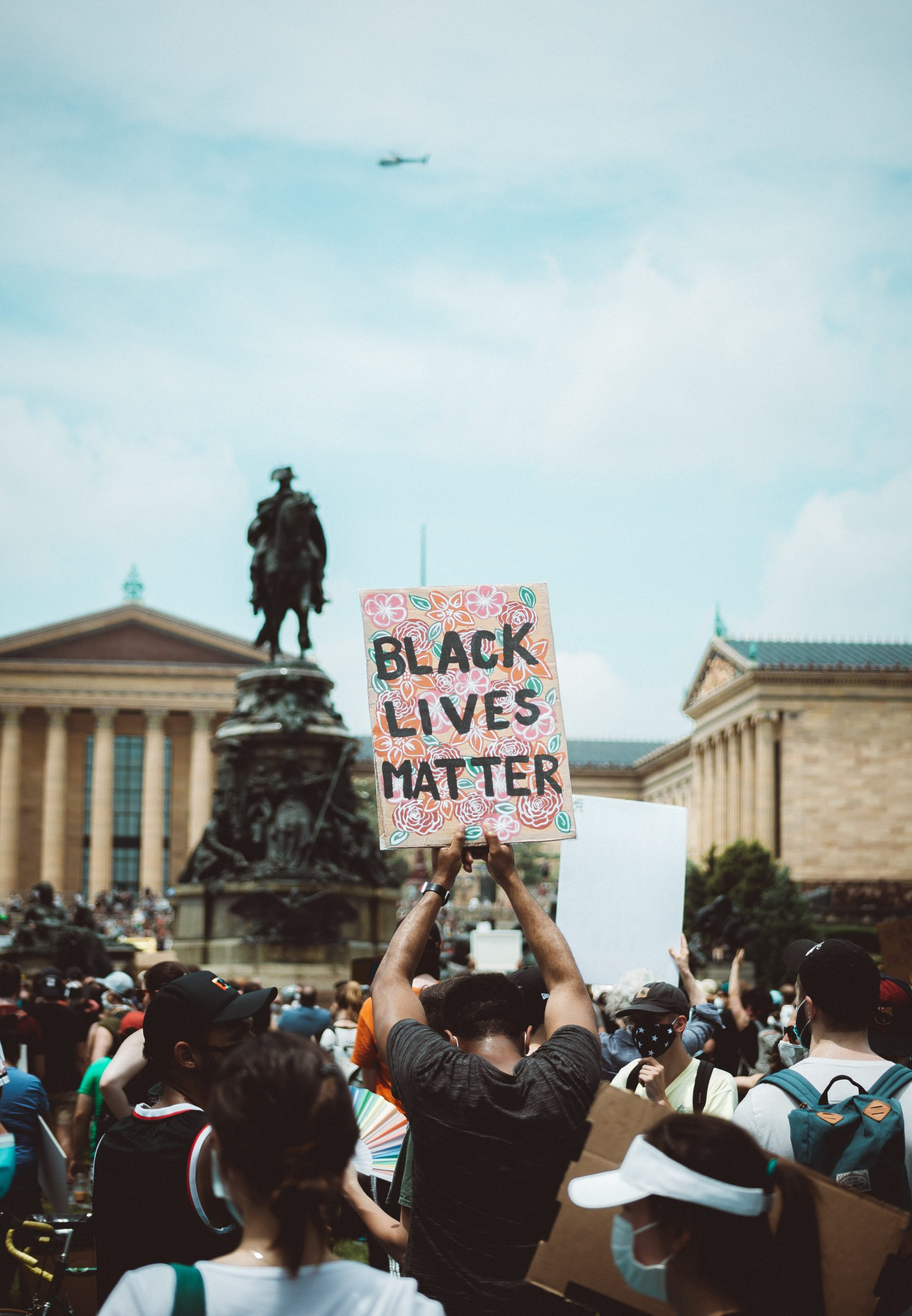 A person holding up a sign of black lives matter